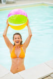 Smiling young woman with beach ball in pool Royalty Free Stock Images
