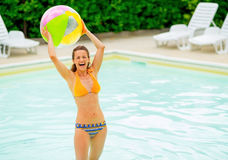 Smiling young woman with beach ball in pool Royalty Free Stock Photos