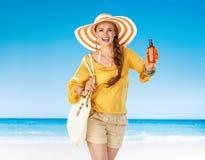 Smiling young woman on beach showing sun screen Stock Photo
