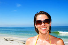 Smiling young woman on a beautiful clear beach Stock Image