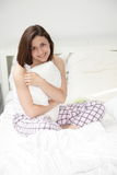 Smiling young woman in bed Stock Photo