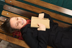 Smiling Young Woman on a Bench with Book. Young happy Caucasian woman lying on a bench reading a book (Selective Focus, Focus on the face Royalty Free Stock Photography