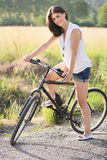 Smiling young woman with bicycle on a country road Stock Photography