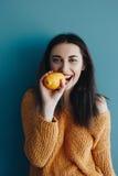 Smiling young woman biting lemon Stock Photos