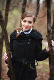 Smiling young woman in a black coat in the autumn park Stock Images