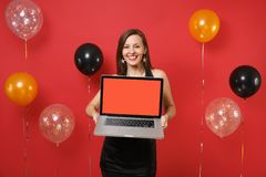 Smiling young woman in black dress celebrating, holding laptop pc computer with blank black empty screen on bright red. Background air balloons. Happy New Year royalty free stock photo