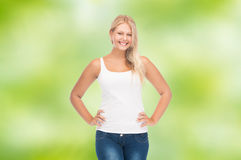Smiling young woman in blank white shirt and jeans. People, holidays, style and body type concept - smiling young woman in blank white shirt and jeans over green Stock Photography