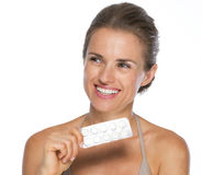 Smiling young woman with blistering package of pills Stock Photo