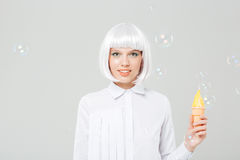 Smiling young woman in blonde wig holding fake ice cream Royalty Free Stock Image