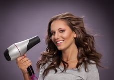 Smiling young woman blow drying her hair. Smiling young woman blow drying her long wavy hair Stock Images