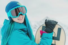 Woman snowboarder in protective sunglasses. Smiling young woman with blue hair in protective sunglasses standing with snowboard on background of snowy mountains stock image