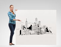Smiling young woman with board and city drawing Royalty Free Stock Photos