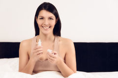 Smiling young woman with a bottle of inhalant Royalty Free Stock Images