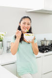 Smiling young woman with a bowl of salad in kitchen Royalty Free Stock Photography