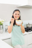 Smiling young woman with a bowl of salad in kitchen Stock Images