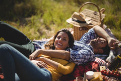 Smiling young woman with boyfriend relaxing on picnic blanket at olive farm Stock Image
