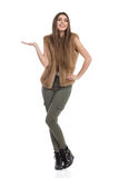 Smiling Young Woman In Brown Fur Vest And Khaki Pants Presenting Royalty Free Stock Image