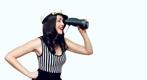 Smiling young woman brunette sailor looks through binoculars, pin-up style on a white royalty free stock photos