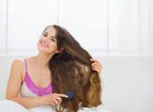 Smiling young woman brushing hair Royalty Free Stock Photos