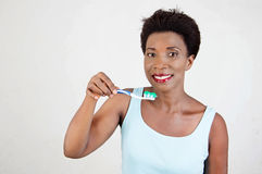 Smiling young woman brushing her teeth. Stock Photo
