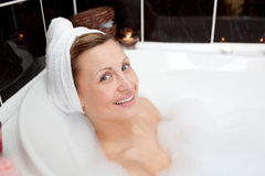 Smiling young woman in a bubble bath Stock Photography