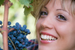 Smiling young woman and bunch of grapes Stock Image