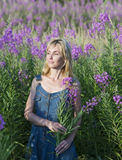 The smiling young woman with bunch of willowherb flower in the field Royalty Free Stock Images
