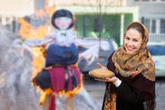A smiling young woman at burning dummy of Maslenitsa Royalty Free Stock Images