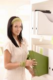 Smiling young woman busy with folders. Smiling young woman busy with arranging folders on shelf, looking at camera Royalty Free Stock Images