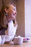 Smiling young woman in cafe. Smiling blonde young woman at the table with a cup of tea Royalty Free Stock Photography