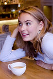 Smiling young woman in cafe. Smiling blonde young woman at the table with a cup of tea Stock Images
