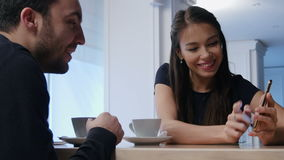 Smiling young woman in cafe showing something on her phone to male friend. Young woman in cafe showing something on her phone to male friend. Close up shot stock video footage