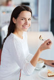 Smiling young woman with cake and coffee at cafe Stock Photography