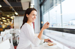 Smiling young woman with cake and coffee at cafe Royalty Free Stock Photography