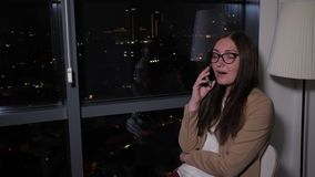 Woman talking phone sitting near the window with panoramic city view at night. Smiling young woman is calling and talking smartphone sitting near the window stock video