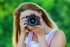 Smiling young woman with camera Stock Photos