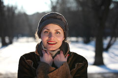 Smiling young woman with a cap. Beautiful young woman in a park in winter time royalty free stock image