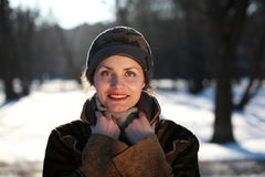 Smiling young woman with a cap. Beautiful young woman in a park in winter time Stock Image