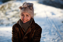 Smiling young woman with cap. Beautiful young woman in a park in winter time Stock Photo