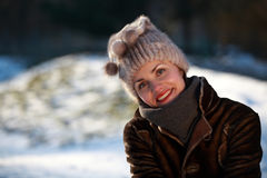 Smiling young woman with cap. Beautiful young woman in a park in winter time Royalty Free Stock Photos