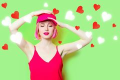 Smiling young woman in cap with hearts royalty free stock photography