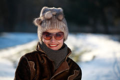 Smiling young woman with cap and sunglasses. Beautiful young woman in a park in winter time Royalty Free Stock Photography