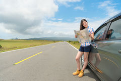 Smiling young woman with car on asphalt roadside. And holding paper map searching travel routes with country street background Stock Photo