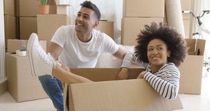 Smiling young woman in a cardboard carton Stock Photo