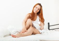 Smiling young woman caring for skin with cosmetic cream in bed Royalty Free Stock Images