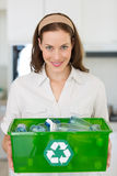 Smiling young woman carrying box with recycling symbol Royalty Free Stock Photography