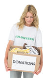 Smiling young woman carrying clothes donation Stock Image