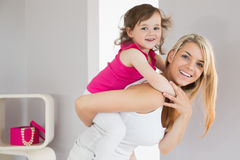 Smiling young woman carrying daughter stock photo