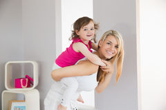 Smiling young woman carrying daughter Royalty Free Stock Photos