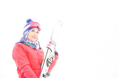 Smiling young woman carrying skis in snow Royalty Free Stock Photography